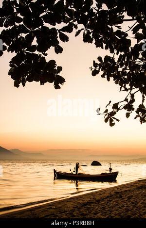 FLORIANÓPOLIS, SC - 02.08.2015: PRAIAS DE FLORIANÓPOLIS - Silhueta de barco e pescador na Praia da Tapera ao por do sol. (Foto: Ricardo Ribas / Fotoarena) - Stock Photo