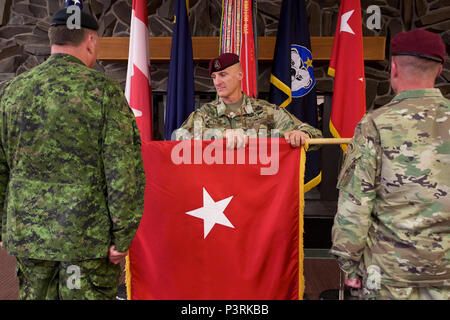 Command Sgt. Maj. Michael Ferrusi (center), U.S. Army Alaska command sergeant major, unfurls a U.S. Army brigadier general flag for Canadian Army Brig. Gen. Martin Frank (left), USARAK deputy commander - operations, as U.S. Army Maj. Gen Bryan Owens, USARAK commander, looks on during the newly minted brigadier general's July 22 promotion at Joint Base Elmendorf-Richardson. Generals and admirals are often called flag officers because of the banner that accompanies them. (U.S. Air Force photo by David Bedard) - Stock Photo