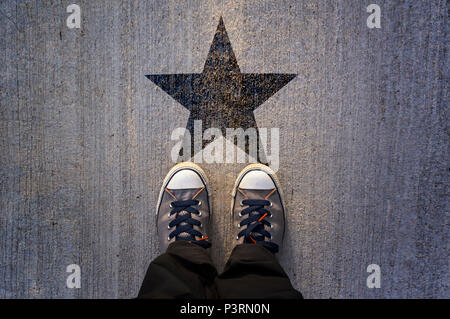Sneakers on asphalt road with black star shape, vip, prize and award concept