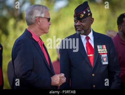 General (Ret)James F. Amos, left, 35th Commandant of the Marine Corps, speaks with a guest during the Montford Point Marine Memorial dedication ceremony held at Jacksonville, N.C.,  July 29, 2016. The memorial was built in honor of the 20,000 African-Americans who attended training at Montford Point. (U.S. Marine Corps photo by Cpl. Laura Mercado) - Stock Photo