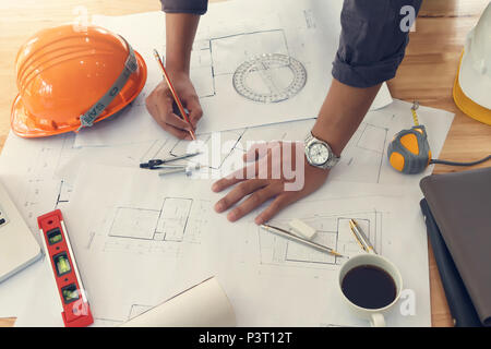 Architect or engineer using pencil working on blueprint, architectural concept - Stock Photo