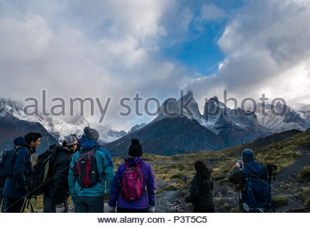 Walking group admiring view and man taking photo, footpath to Cuernos lookout, Paine Horns, Torres del Paine National Park, Patagonia, Chile - Stock Photo