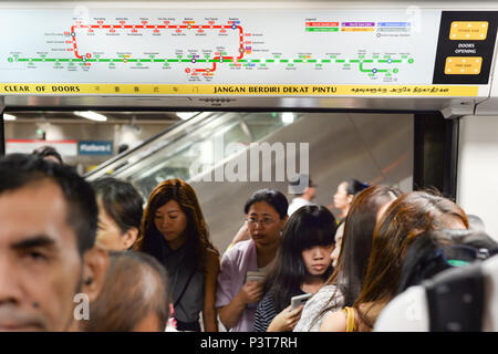 SINGAPORE - FEBRUARY 18, 2017: Passengers boarding train at am metro station in Singapore. The MRT has 102 stations and is the second-oldest metro sys - Stock Photo