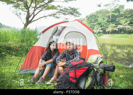 couple traveling and spending time while camping - Stock Photo