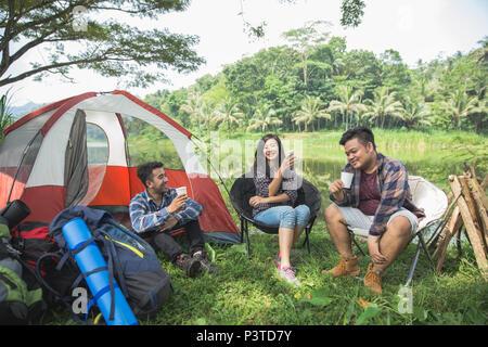 Friends Relaxing Outside Tents On Camping - Stock Photo