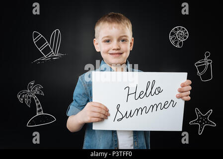 Cute boy smiling and showing a hello summer sign - Stock Photo