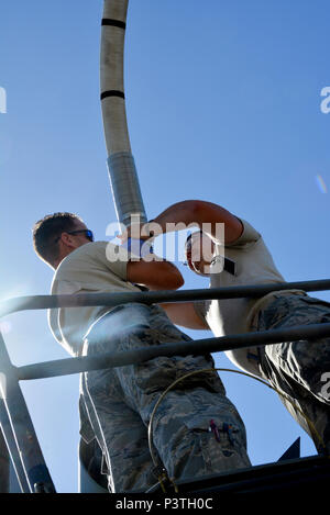 JOINT BASE PEARL HARBOR-HICKAM (July 10, 2016) (from left to right) Staff Sgt. James Andrus and Senior Airman Travis Krause, U.S. Air Force crew chiefs with the 507th Aircraft Maintenance Squadron at Tinker Air Force Base, Okla., connect a drogue adapter to a KC-135R Stratotanker in order to connect a drogue. A drogue is used in air-to-air refueling. The probe and drogue method of refueling uses a trailing hose with a basket on the end. Pilots guide a probe on their aircraft into the basket to connect with the hose. Air Force helicopters, and all Navy and Marine Corps aircraft refuel using the - Stock Photo