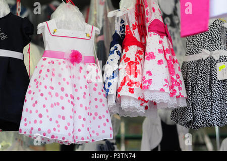 little girls dresses in a market stall, market in the south of Italy - Stock Photo