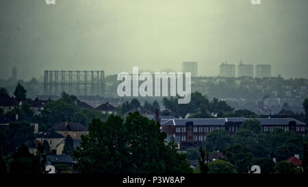 Glasgow, Scotland, UK 20th June. UK Weather: Midsummer approaches and autumnal wet foggy cold weather as only the suburb houses of Knightswood are totally visible in front of  the Kelvinside gasometers and the towers of maryhill while the city is invisible under the fog and rain in the distance, Gerard Ferry/Alamy news Credit: gerard ferry/Alamy Live News - Stock Photo
