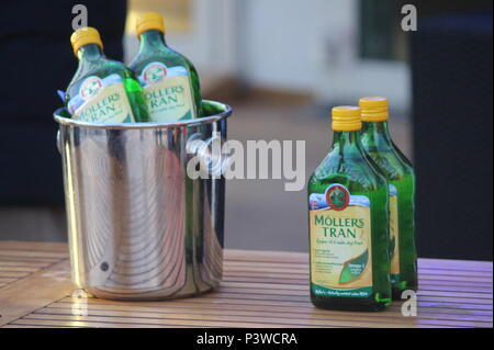 Four bottles of Moller's Tran Cod liver oil, tow on table and two in stainless steel ice bucket taken on Hurtigruten cruise crossing the Artic circle - Stock Photo