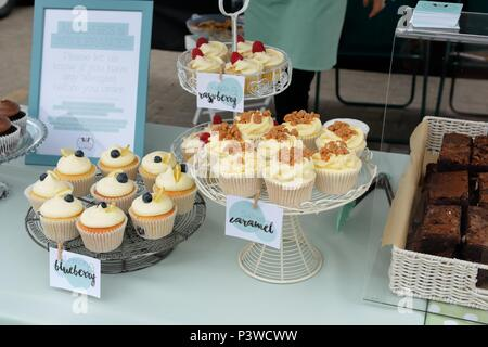 Cake stands at a local food fair in Portree, Skye, Scotland, with assorted fresh cupcakes and a notice warning of possible nut allergy contents. - Stock Photo