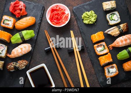 Sushi, maki, nigiri and sushi roll set on dark stone table top view. Japanese food. - Stock Photo