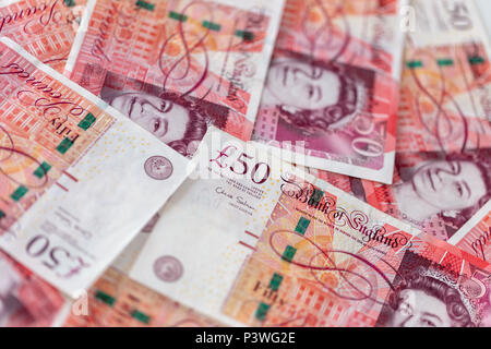 Background of scattered fifty pound bank notes sterling - Stock Photo