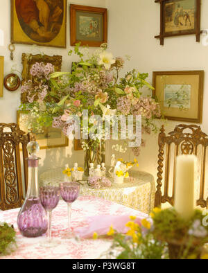 Pictures above vase of summer flowers on corner table in cottage dining room with amethyst glasses and decanter - Stock Photo