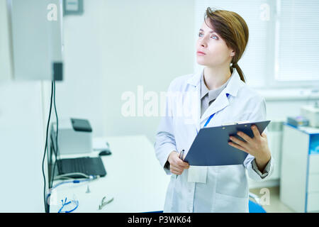 Doctor standing with clipboard and looking at something - Stock Photo