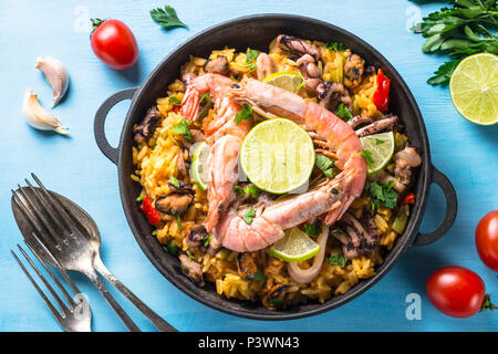 Seafood paella. Traditional spanish dish, european cuisine. Top view on blue table. Stock Photo