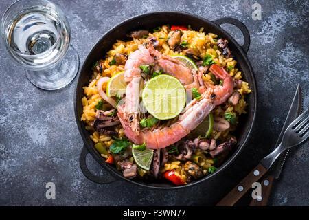 Seafood paella. Traditional spanish dish, european cuisine. Top view on dark stone table. - Stock Photo