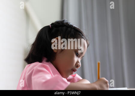 Close up the little girl is doing homework intently. Children use a yellow pencil is writing a notebook. Select focus shallow depth of field with copy - Stock Photo
