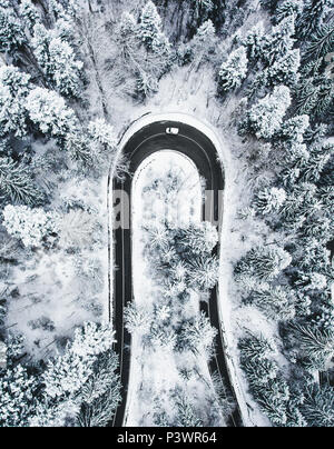 White car passing on an extreme winding road in wintertime - Stock Photo