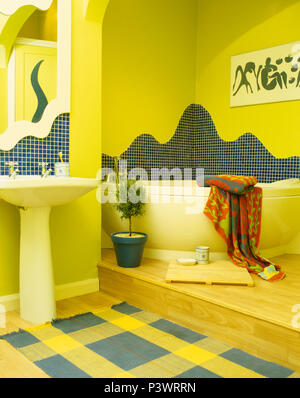 Mosaic tiling above corner bath in yellow split-level bathroom with yellow+blue checked rug below pedestal basin - Stock Photo
