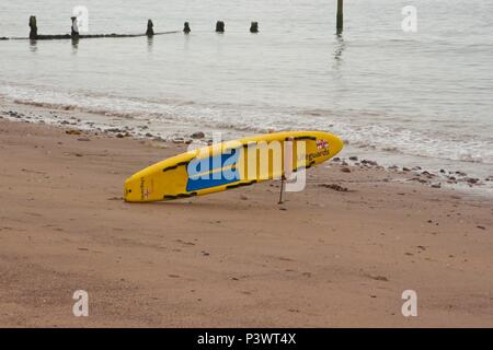 A RNLI lifeguard surf board propped up on the beach at Teignmouth, South Devon - Stock Photo