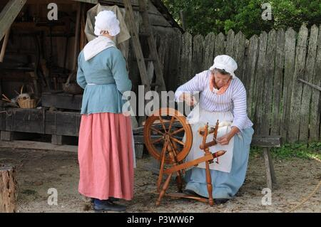 American pioneer spinning thread on a spinning wheel - Stock Photo