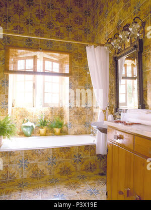 White shower curtain on bath in blue+yellow tiled bathroom with open windows above the bath - Stock Photo