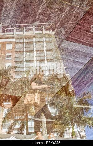Reflexo de mulher e edifício em espelho d'água na Cidade Pedra Branca, um empreendimento imobiliário sustentável na Grande Florianópolis. Palhoça, Santa Catarina, Brasil. - Stock Photo