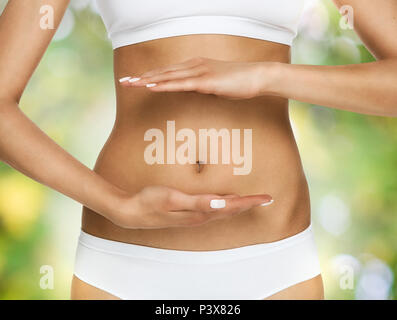 Pregnancy or diet concept, female hands protecting the stomach over nature background - Stock Photo