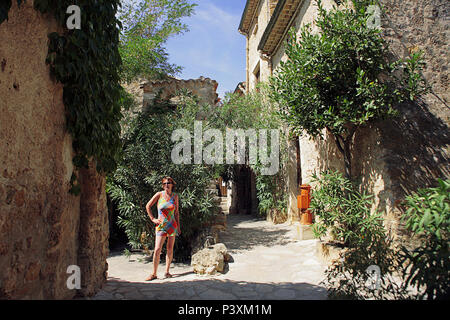 A woman poses in quiet lane (Rue du Teron) in the medieval village of Saint-Guilhem-le-Désert; Hérault, Occitanie, France.  MODEL RELEASED