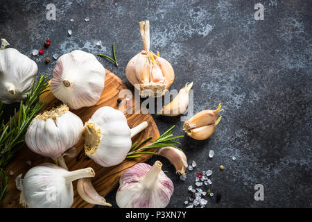 Garlic cloves with spices and herbs on a dark stone background. Top view, Copy space. - Stock Photo