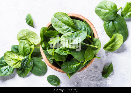 Baby spinach on gray stone table. Top view. - Stock Photo