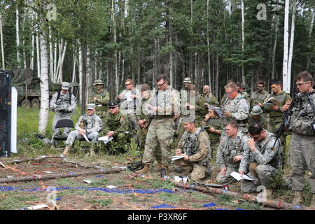 Maj. Gen. Bryan Owens, commander of U.S. Army Alaska Canadian Army Col. Martin Frank, the Deputy Commander-Operations for U.S. Army Alaska and Soldiers from1st Stryker Brigade Combat Team 'Arctic Wolves', and Bravo Company, 1st Battalion, Princess Patricia's Canadian Light Infantry participate in an operations order brief at the brigade tactical operations center during Rotation 16-02 Arctic Anvil. - Stock Photo