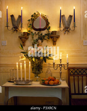 Lighted candles in wall lights on either side of mirror above painted table with vase of summer flowers - Stock Photo