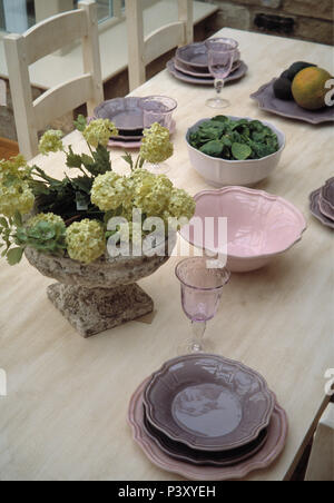 Close-up of mauve and pink crockery on limed wood table with green hydrangeas in stone vase - Stock Photo