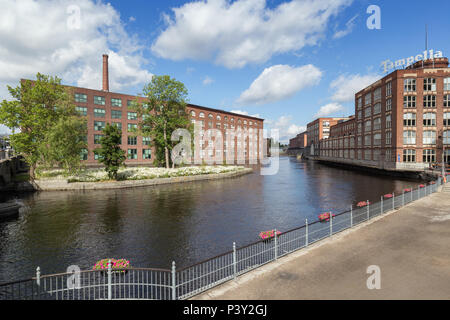 Old red brick industrial buildings along the Tammerkoski rapids in downtown Tampere, Finland on a sunny day. - Stock Photo
