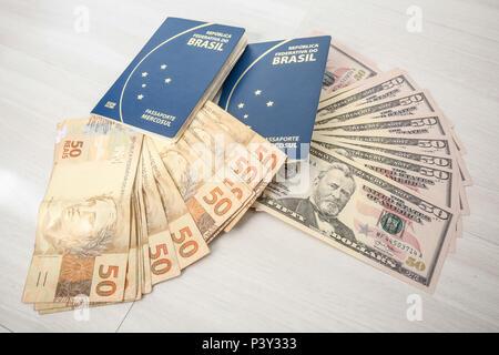 Dólar ao lado de passaporte. O dólar americano é a moeda emitida pelos Estados Unidos e tem sua emissão controlada pela Reserva Federal daquele país. O dólar é usado tanto em reservas internacionais como em livre circulação. - Stock Photo