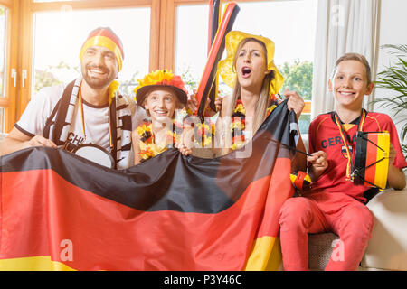 Whole family cheering for the German soccer team in front of TV - Stock Photo