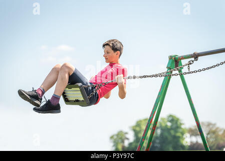 Teen boy swinging high having fun in British playground on sunny bright day - Stock Photo