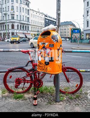 Urban still life - red parked bicycle & sticker covered orange rubbish bin at Rosenthaler Platz,Mitte, Berlin - Stock Photo