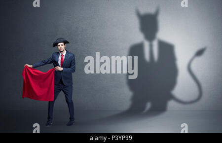 Businessman standing with red cloth in his hand and devil shadow on the background  - Stock Photo
