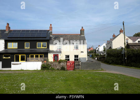 Modern house with photovoltaic cells and traditional cottage with red gate  in the village of Marloes in Pembrokeshire West Wales, UK  KATHY DEWITT - Stock Photo