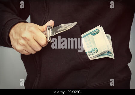 A man with a knife in his hand and a thousand rubles in his pocket. Russian mafia. - Stock Photo