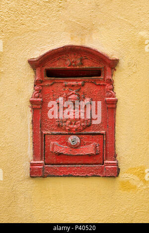 Old red Mailbox  cracked and rusting on yellow wall - Stock Photo