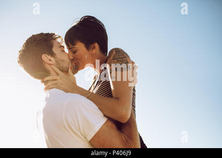 Beautiful couple kissing outdoors. Affectionate woman kissing her boyfriend. - Stock Photo