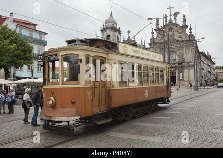 Traditional vintage tram at the Carmo Stop in Porto, Portugal. The Carmo Church (Igreja do Carmo) is seen in the background. - Stock Photo