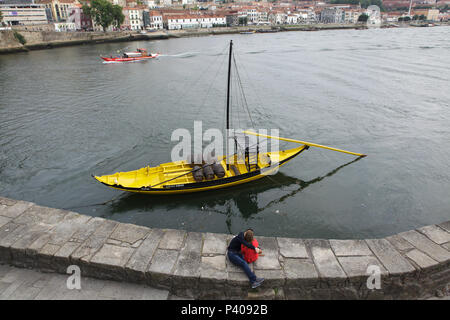 Couple kissing on the embankment of the River Douro next to the typical yellow rabelo boat used to transport port wine in Porto, Portugal. - Stock Photo
