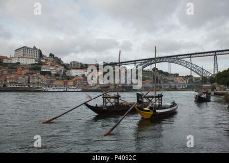 Typical rabelo boats used to transport port wine on the River Douro in Porto, Portugal. The Dom Luís I Bridge (Ponte de Dom Luís) designed by German engineer Théophile Seyrig is seen in the background. - Stock Photo