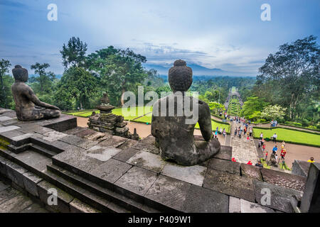 a serene sitting Buddha watches on as visitor crowds mak their way to the ascend of 9th century Borobudur Buddhist temple, Central Java, Indonesia - Stock Photo