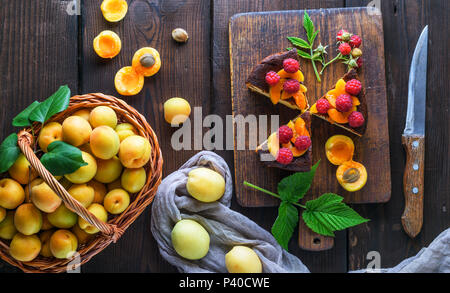 fresh apricots and pieces of cheesecake on a brown wooden board, top view - Stock Photo